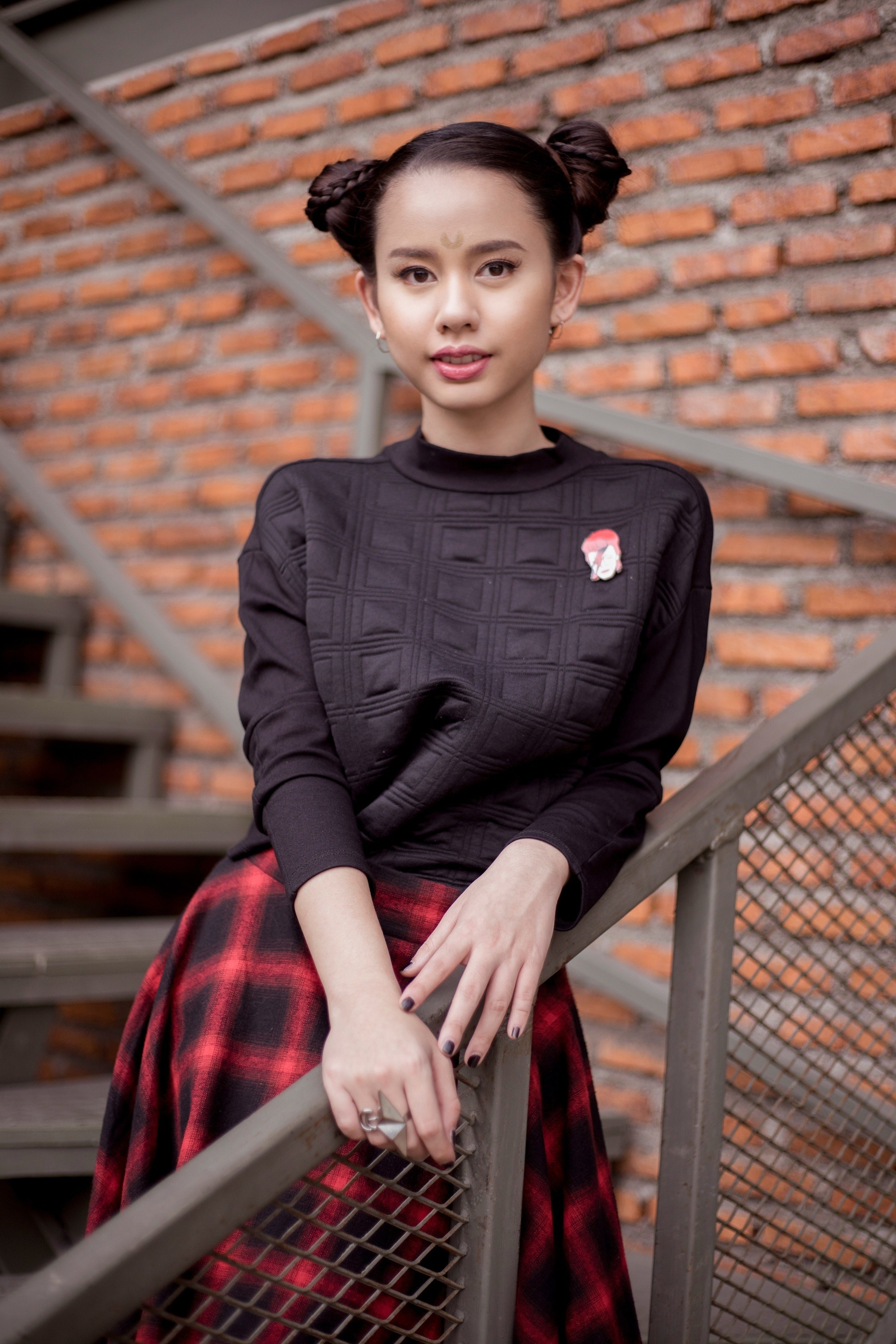Halloween glam hair: Asian girl with black hair in double buns wearing black jacket and plaid skirt against a brick wall in outdoor location