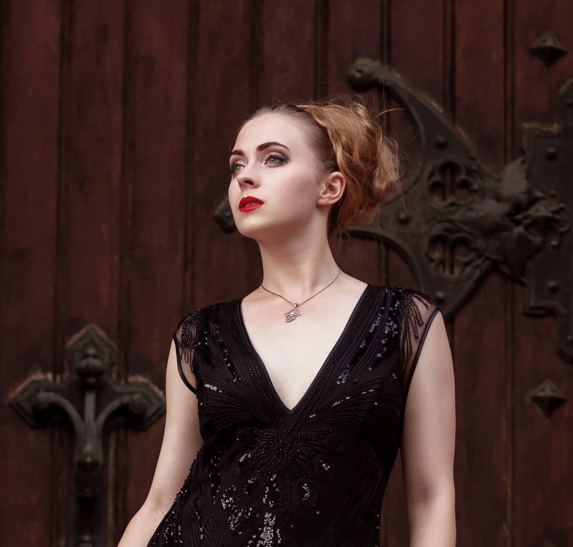 Halloween glam hair: Woman with brownish blonde hair in a big bun wearing a long black dress and standing against a wooden door in an outdoor location