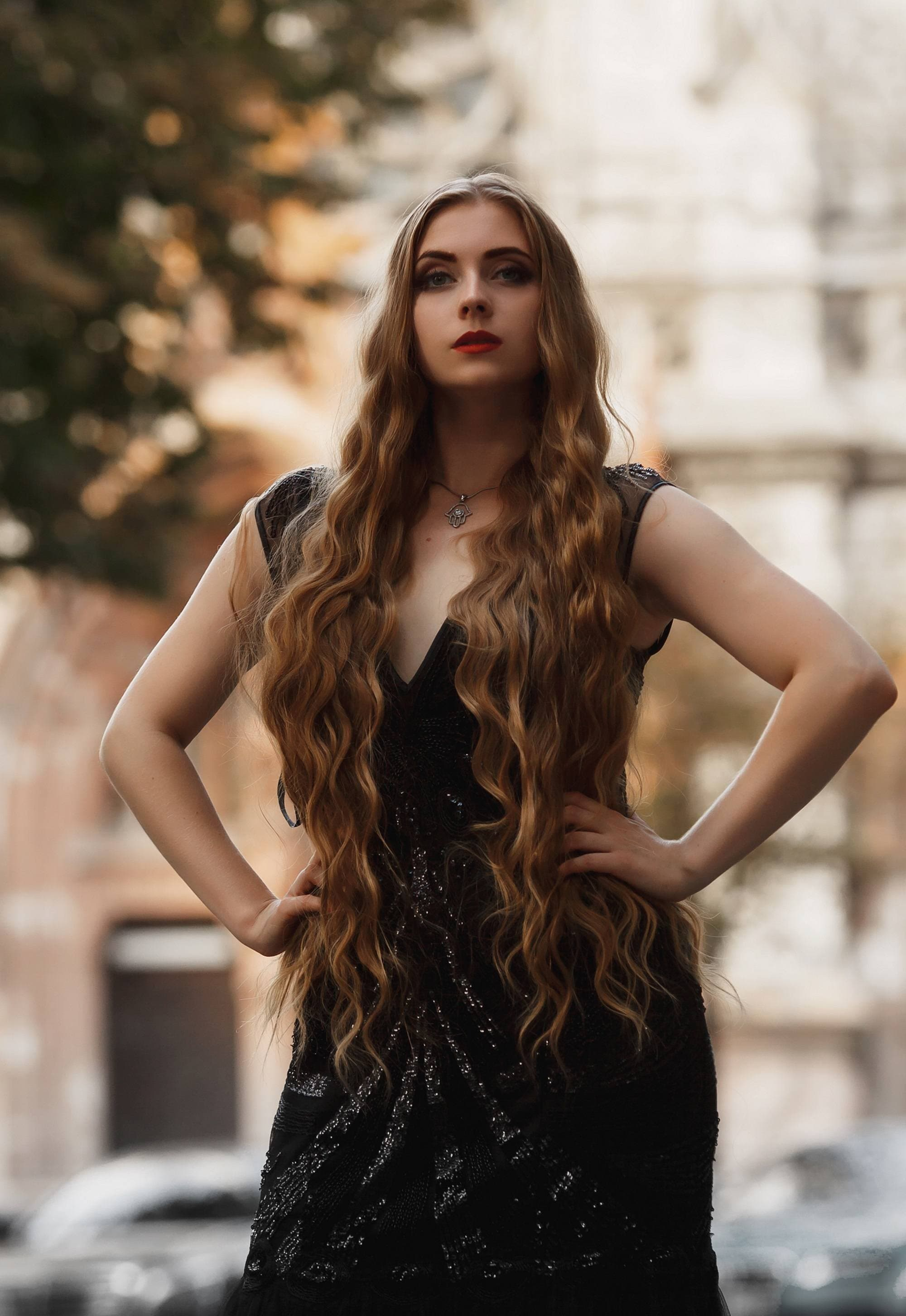 Halloween glam hair: Woman with long brownish blonde wavy hair, wearing a black dress, with hands on her hips in outdoor location