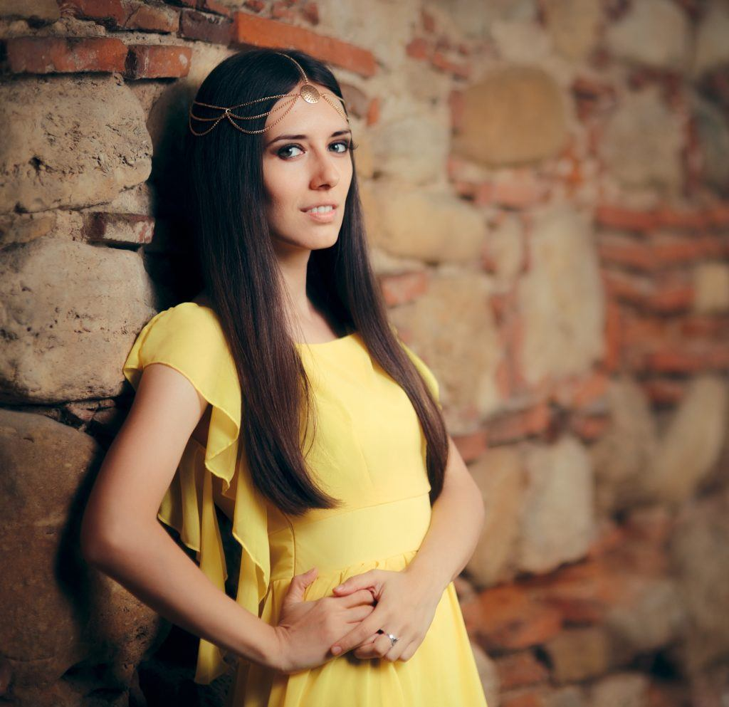 Halloween glam hair: Woman with long straight, black hair wearing a yellow dress and gold, minimalist headpiece standing against stone wall background in an outdoor location