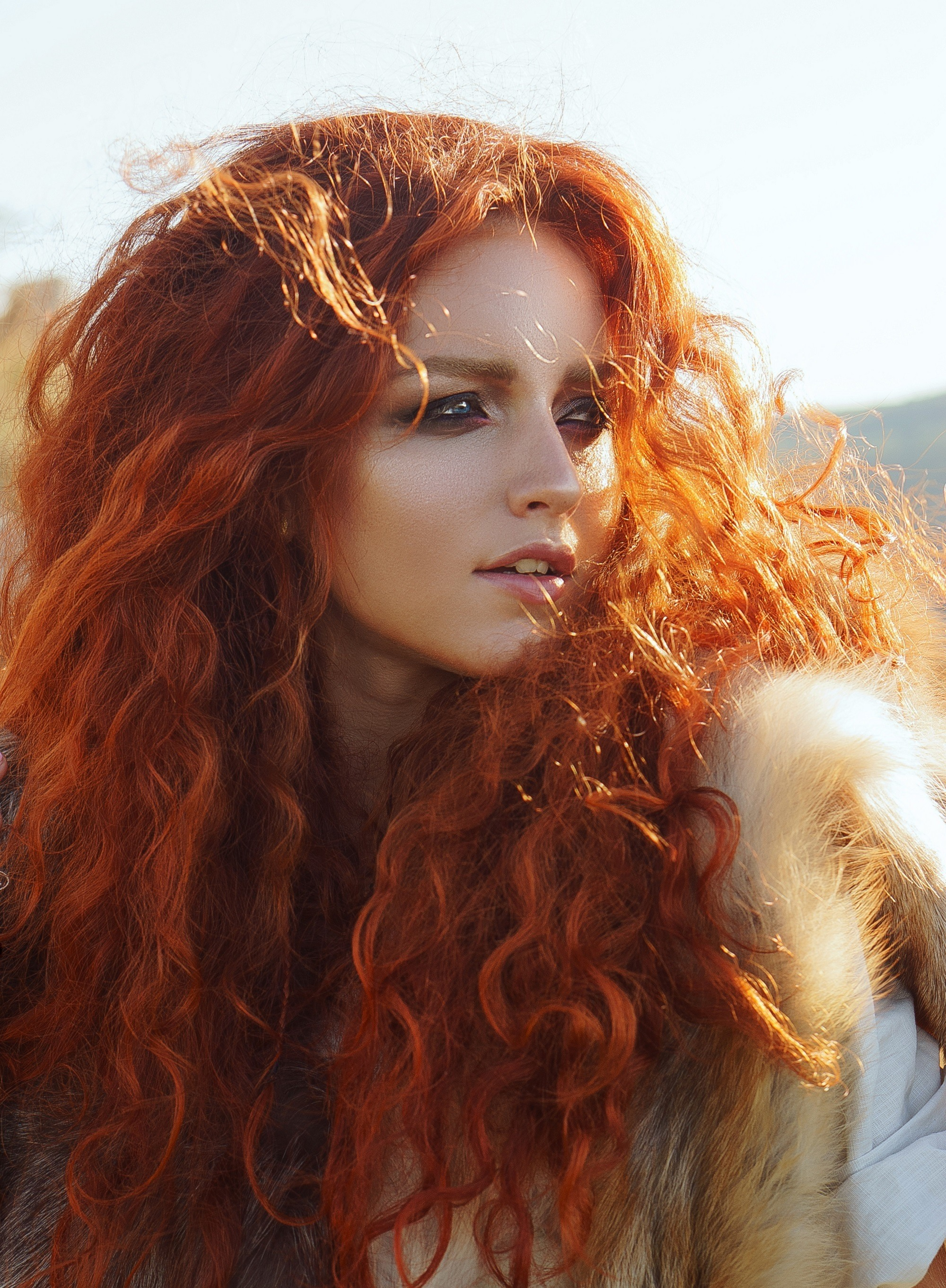 Halloween glam hair: Woman with long red thick curly hair looking at the side in outdoor location
