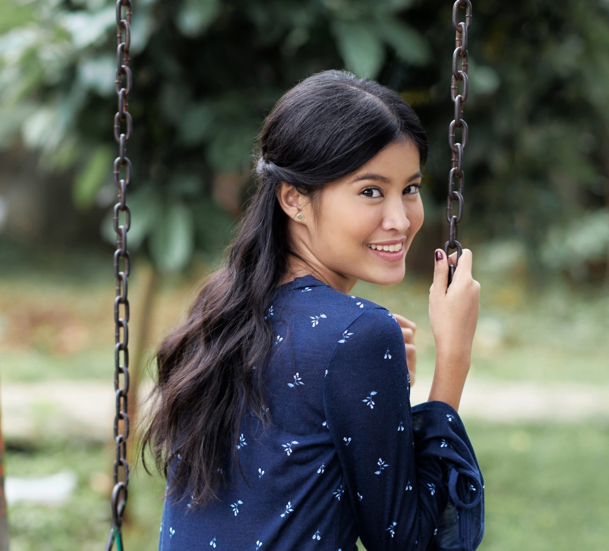 Long black hair: Asian woman wearing a dark blue dress with long black hair sitting on a swing in a park