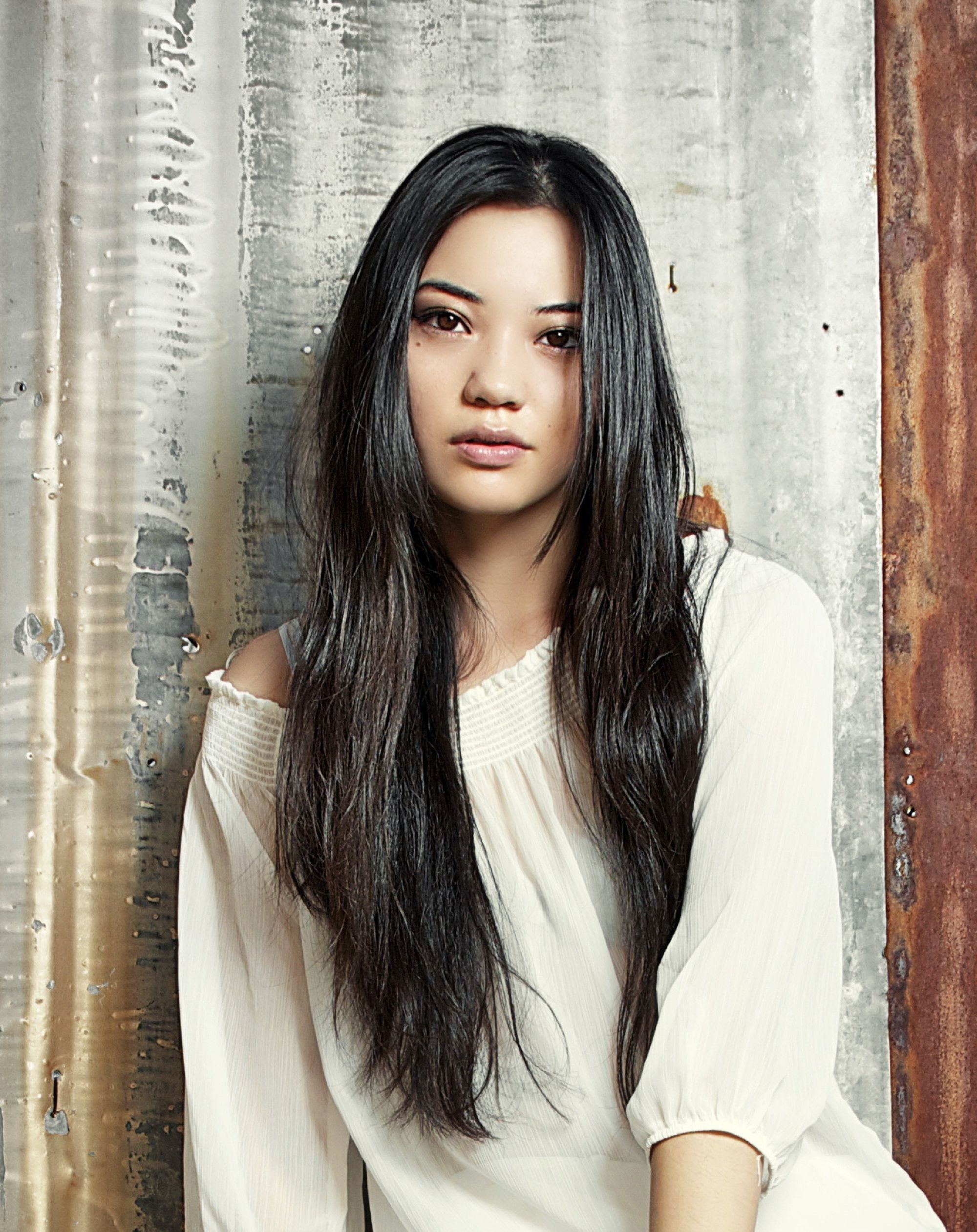 Long black hair: Woman wearing a white blouse with long black hair standing against an iron roof background