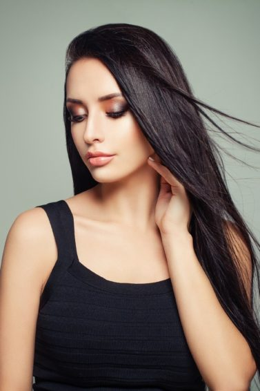 Long black hair: Closeup shot of a woman with long black straight hair wearing a sleeveless black top