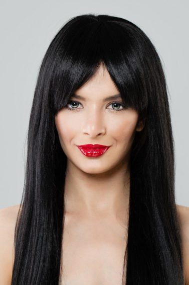 Long hair with bangs: Closeup shot of a woman with long black hair with curtain bangs against a gray background