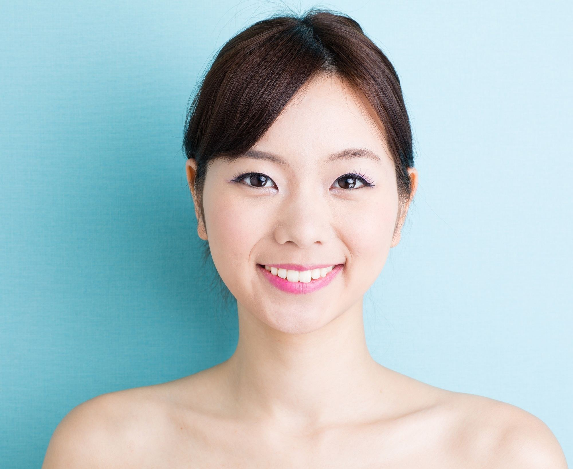 Long hair with side bangs: Closeup of an Asian woman with black hair in a bun against a blue background