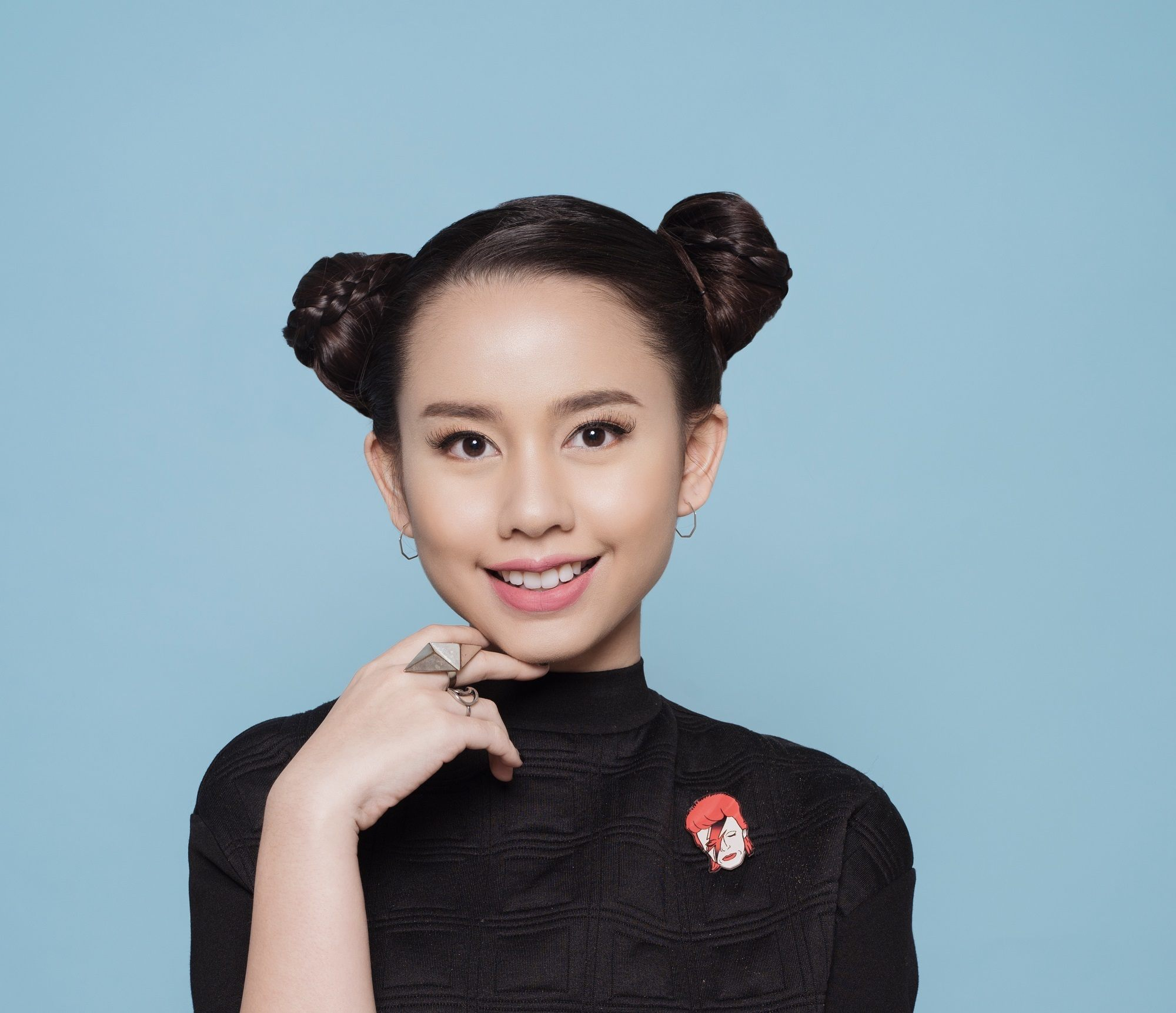 Asian girl with hair in two side buns against blue background to represent users of new Sunsilk Smooth and Manageable Shampoo