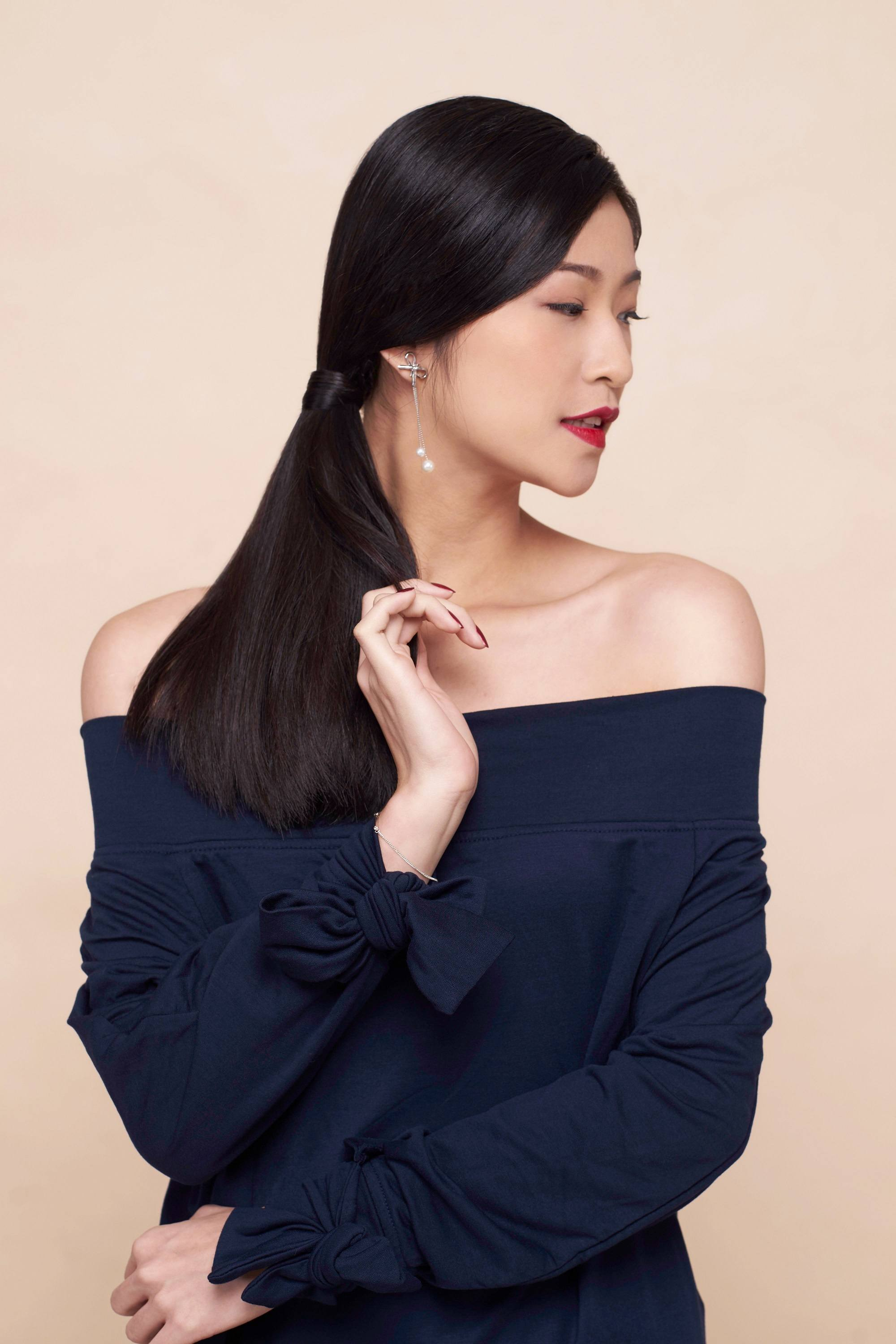 Asian woman wearing navy blue blouse with long black hair in side ponytail standing against a, peach background to represent users of serum conditioners