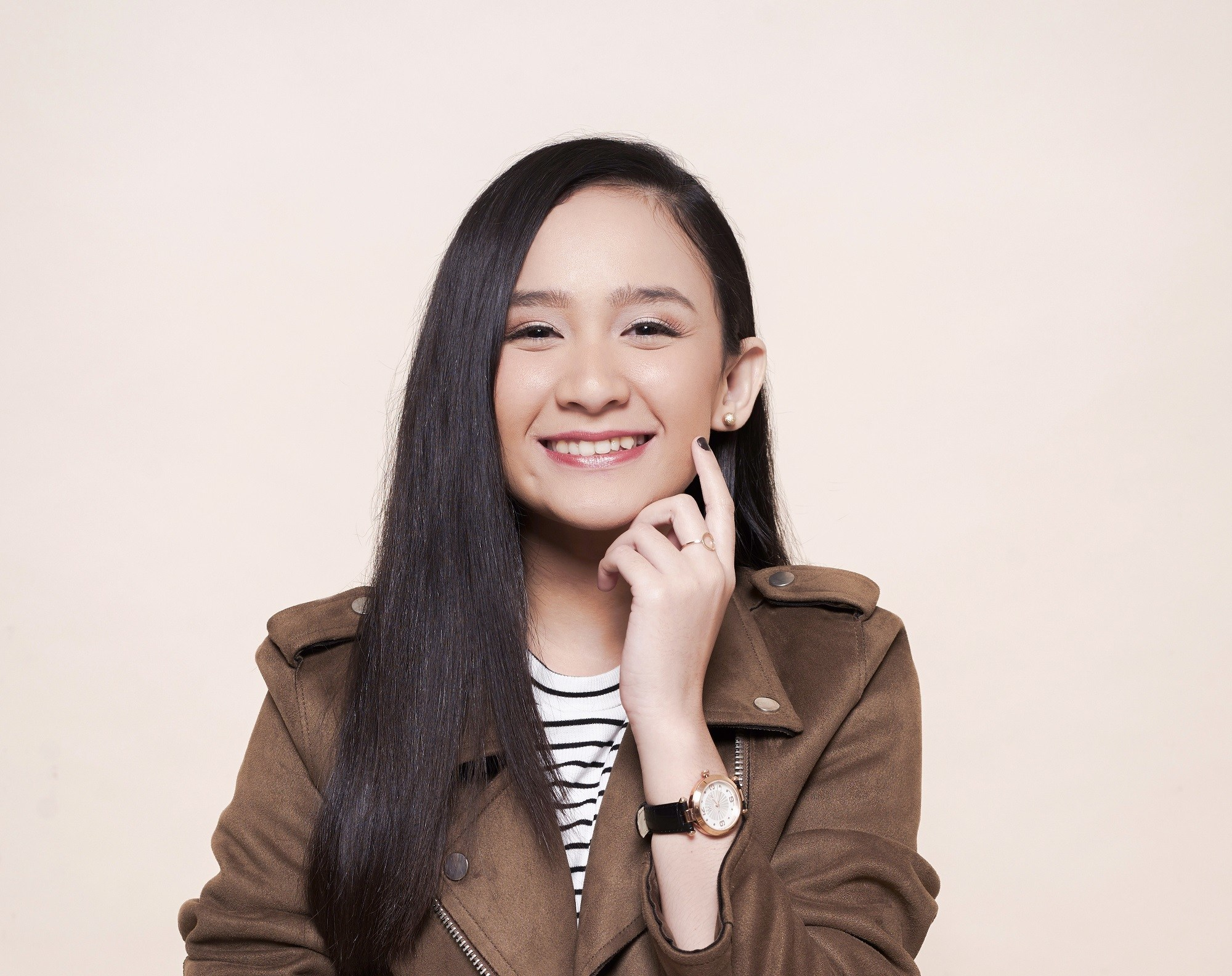 Asian girl with long straight black hair wearing a brown jacket standing against an oyster-colored background to represent users of serum conditioners