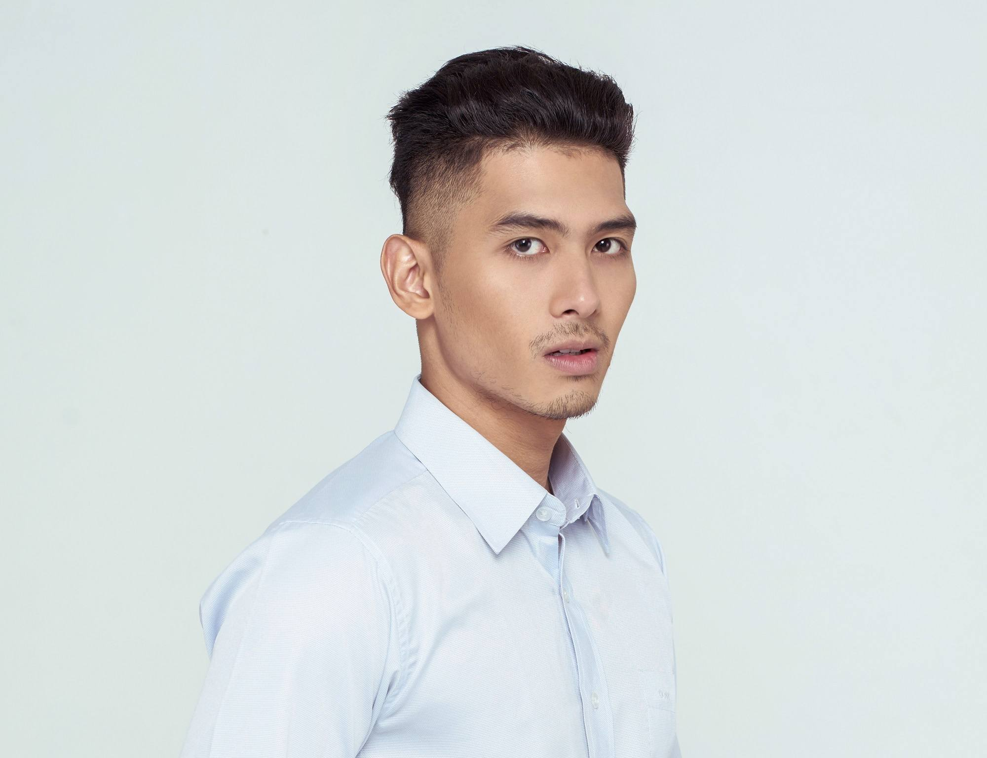 Shaved side hairstyles men: Asian man wearing a white collared polo with shaved side hairstyle and short hair standing against a white background