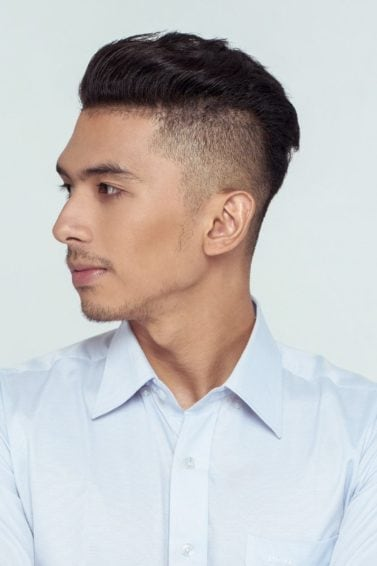 Shaved side hairstyles men: Asian man wearing a white long-sleeved polo with shaved side hairstyle and short hair against white background