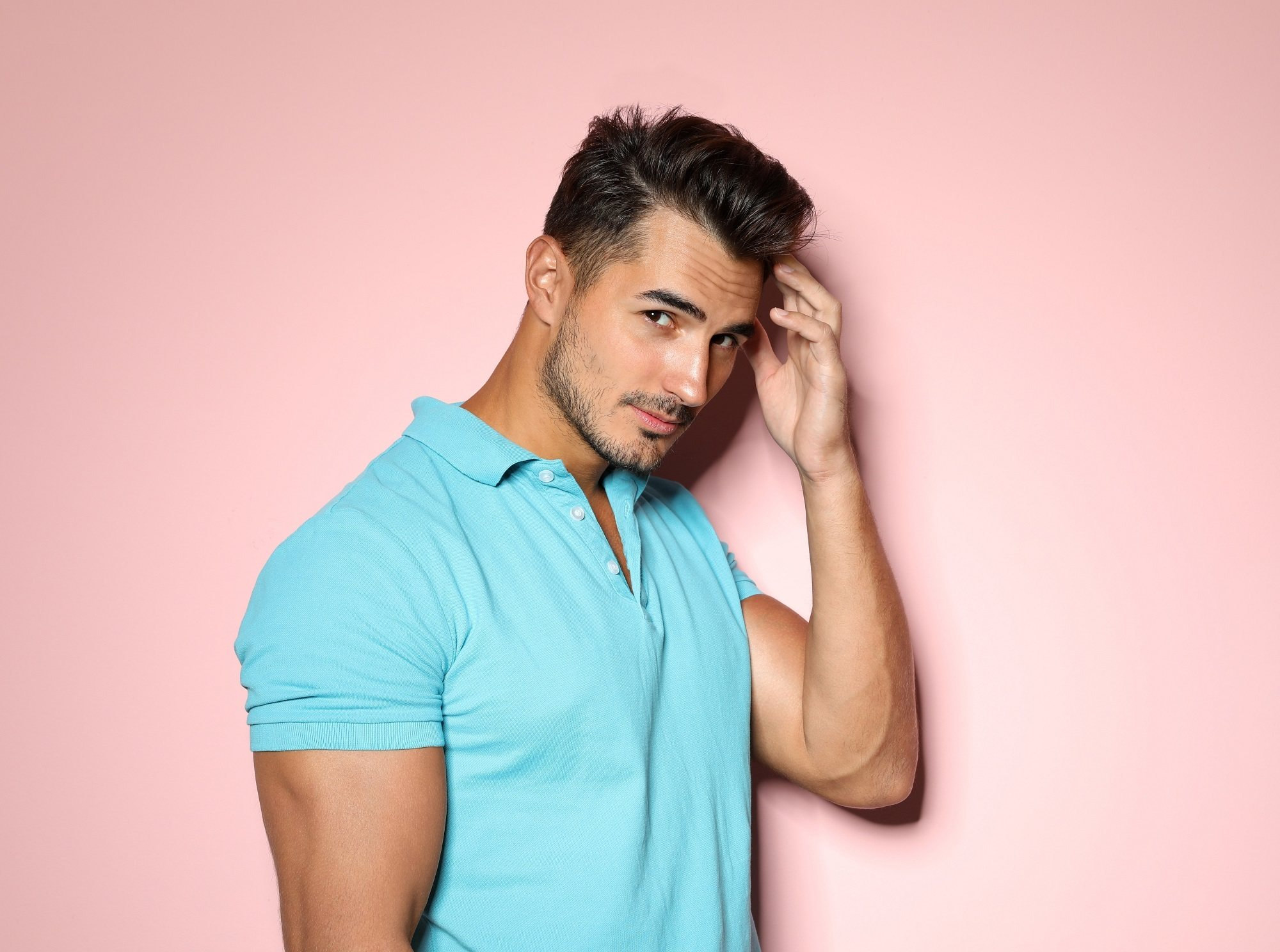 Shaved side hairstyles men: Main wearing a blue polo shirt touching his hair and standing against a pink background