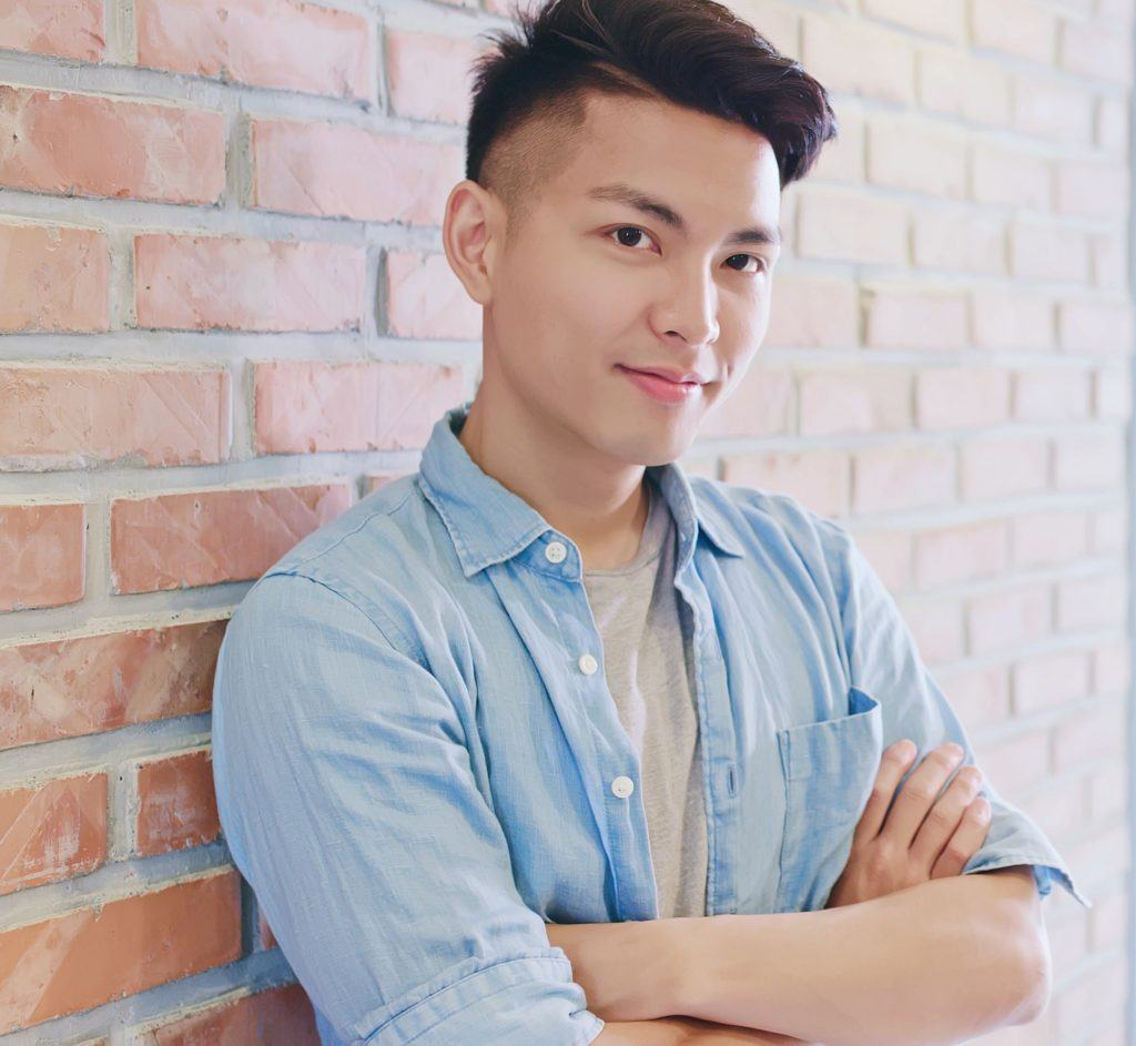Shaved side hairstyles men: Man wearing a blue polo over a white shirt with a faded haircut standing against a brick wall