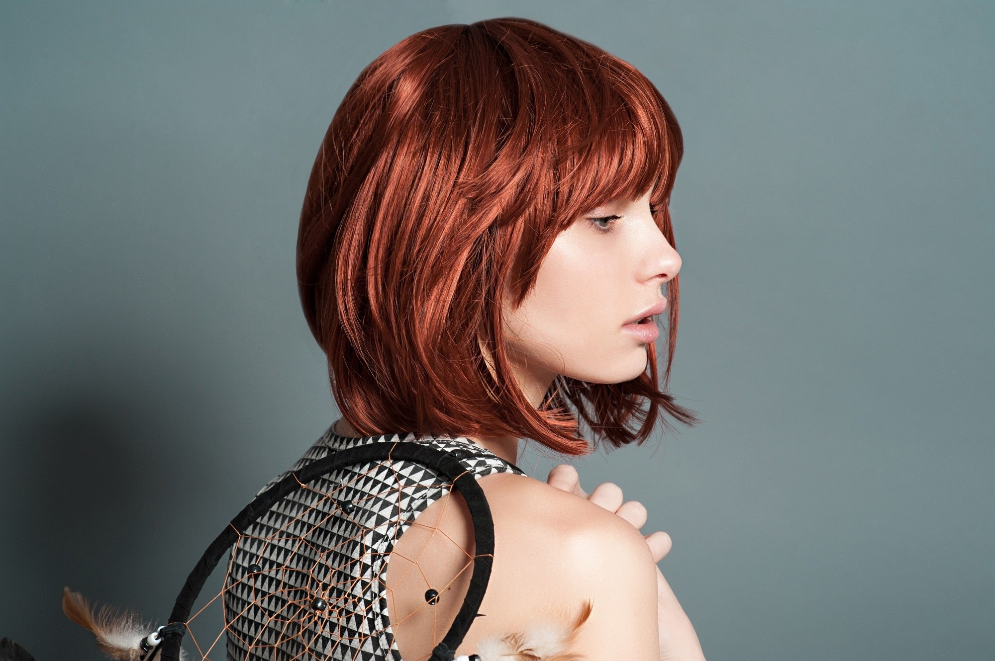 Shot red hair: Woman with dark copper bob with bangs