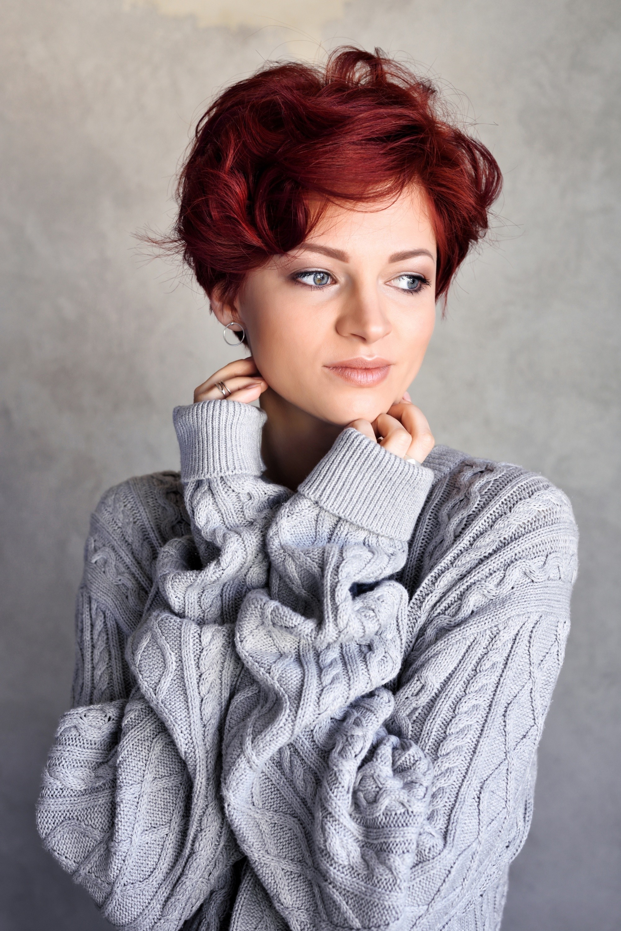 Short red hair: Woman with red tousled pixie cut wearing a gray sweater