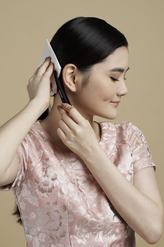 Sleek low bun with side part: Asian woman clipping her hair