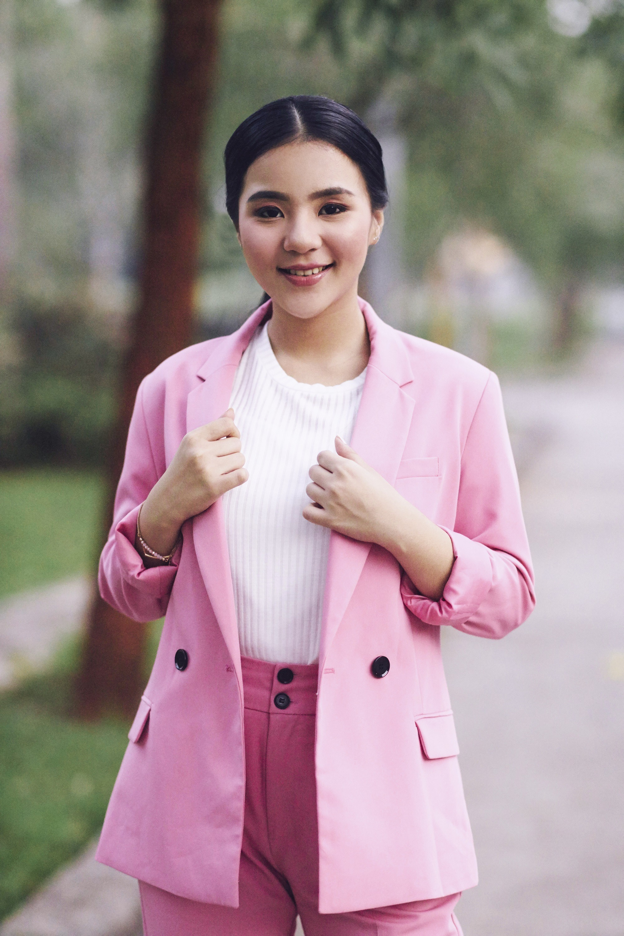Tucked in ponytail. Asian woman wearing white blouse and pink blazer and pants with long black hair in tucked in ponytail standing ioutdoors