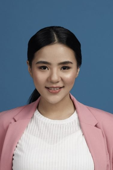 Tucked in ponytail: Asian woman wearing white blouse and pink blazer with long black hair in ponytail standing against a blue background