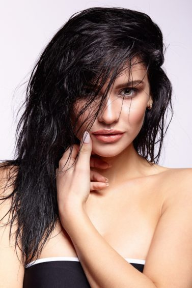 Wet hair look: Closeup shot of a woman with long messy black hair wearing a black tube top against a white background