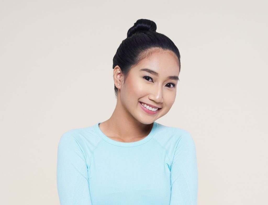 Advent calendar: Closeup shot of an Asian woman with long black hair in a bun wearing light blue shit against an oyster-colored background