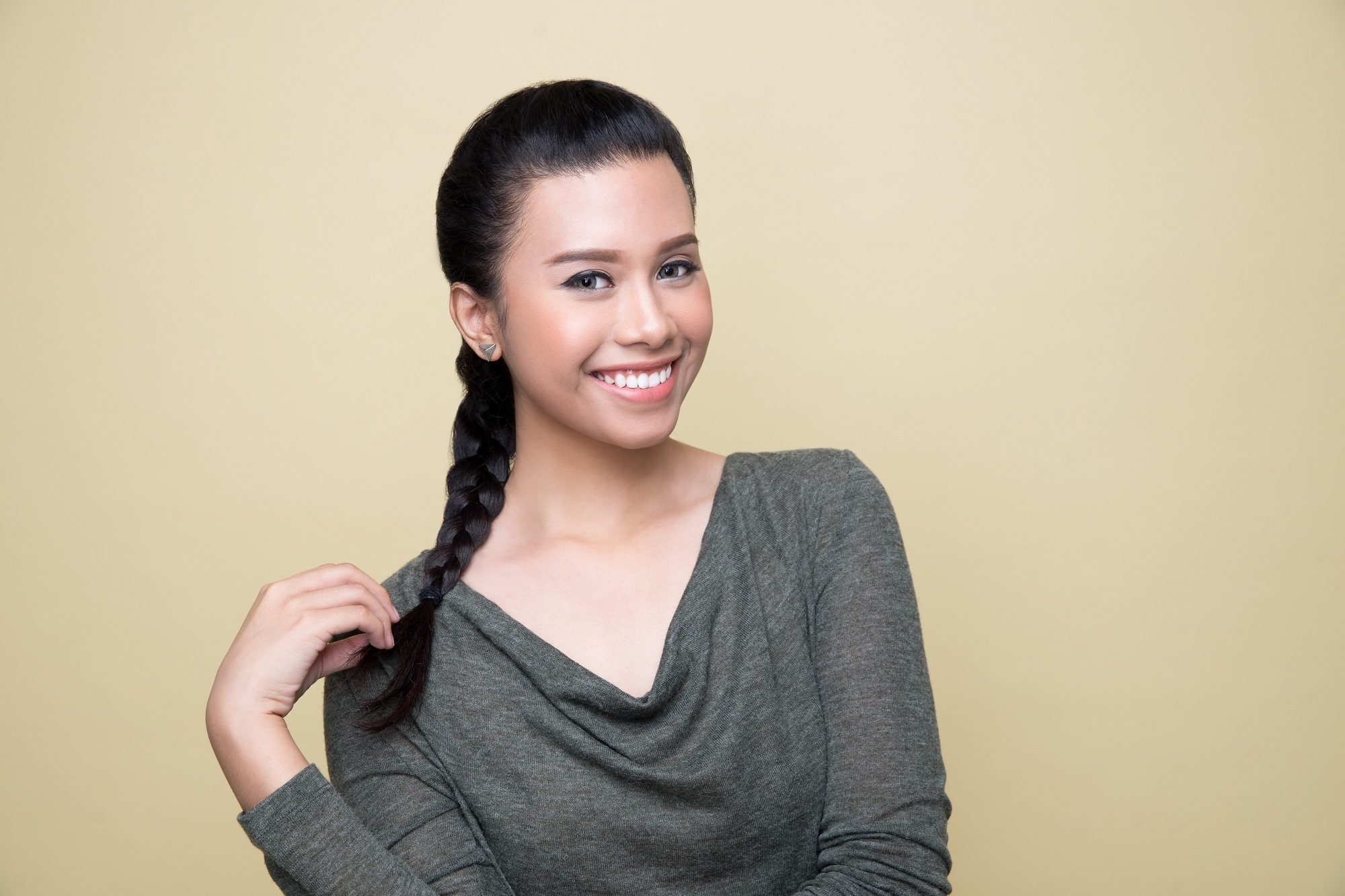 Advent calendar: Closeup shot of an Asian woman with long hair in French braid wearing a gray long-sleeved top