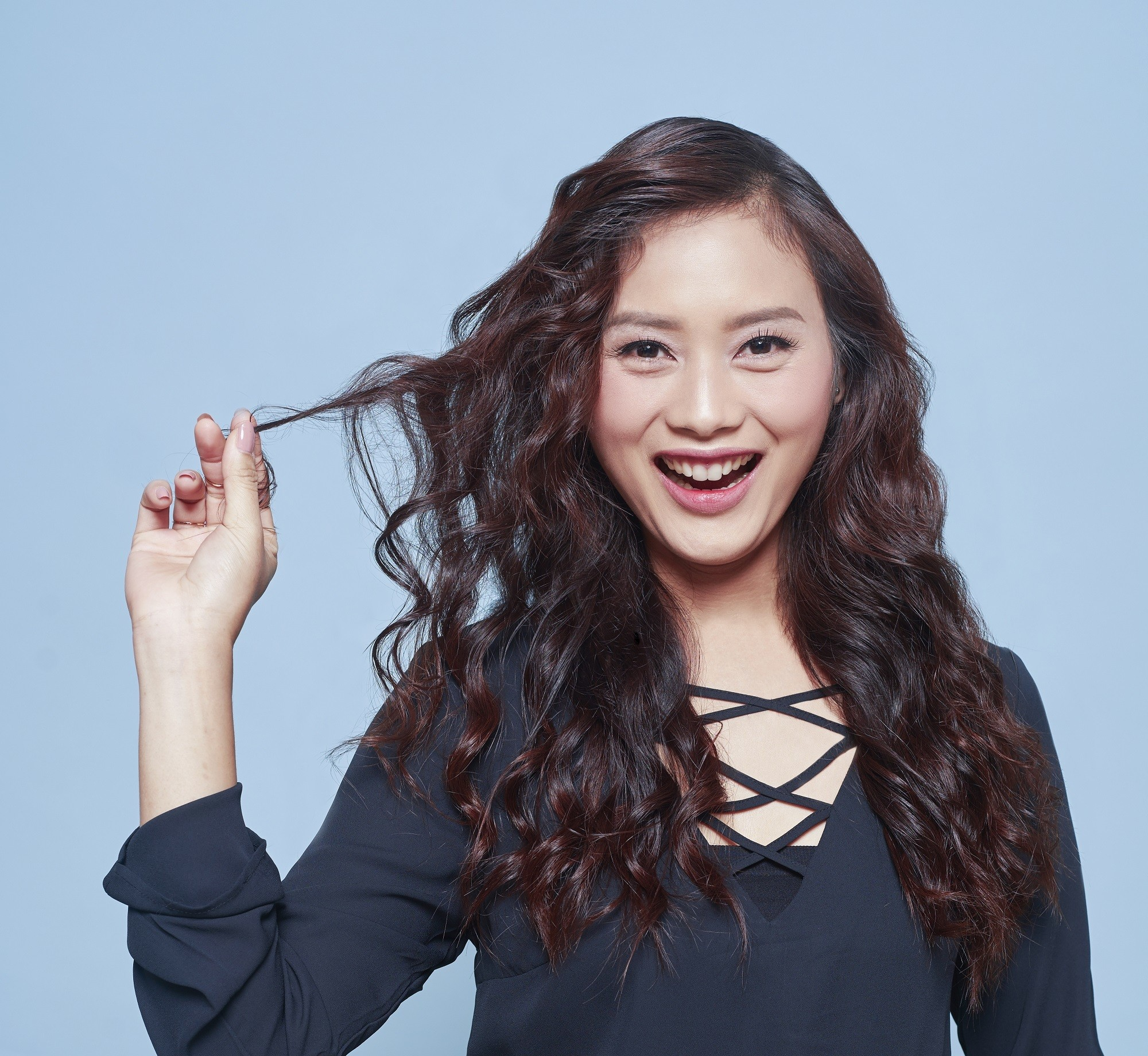 Advent calendar: Closeup shot of an Asian woman with long dark brown wavy hair wearing a long-sleeved top