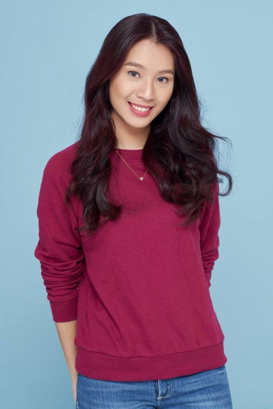 Banana bun: Asian woman wearing a red sweater and denim pants with long black hair standing against a blue background
