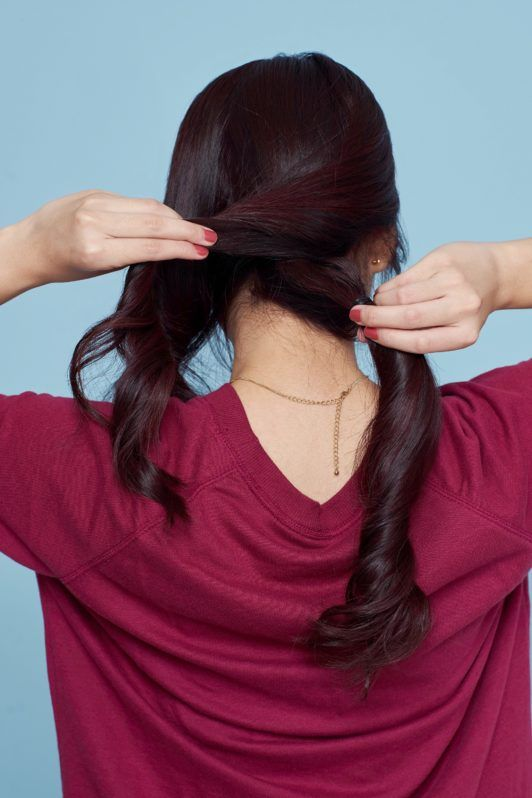 Banana bun: Back shot of an Asian woman wearing a red sweater styling her hair standing against a blue background
