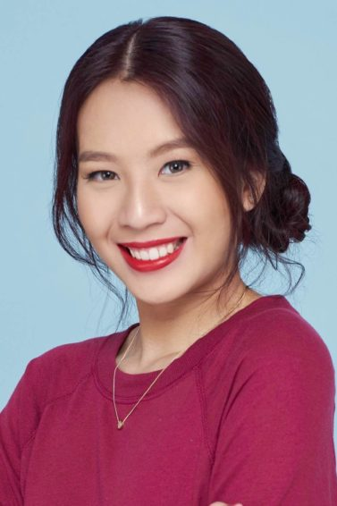 Banana bun: Closeup shot of an Asian woman wearing a red sweater with hair on a banana bun against a blue background
