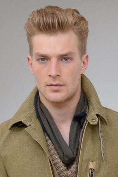Best hair color for men: Closeup shot of Caucasian man with ash brown hair wearing an olive green jacket against a gray background