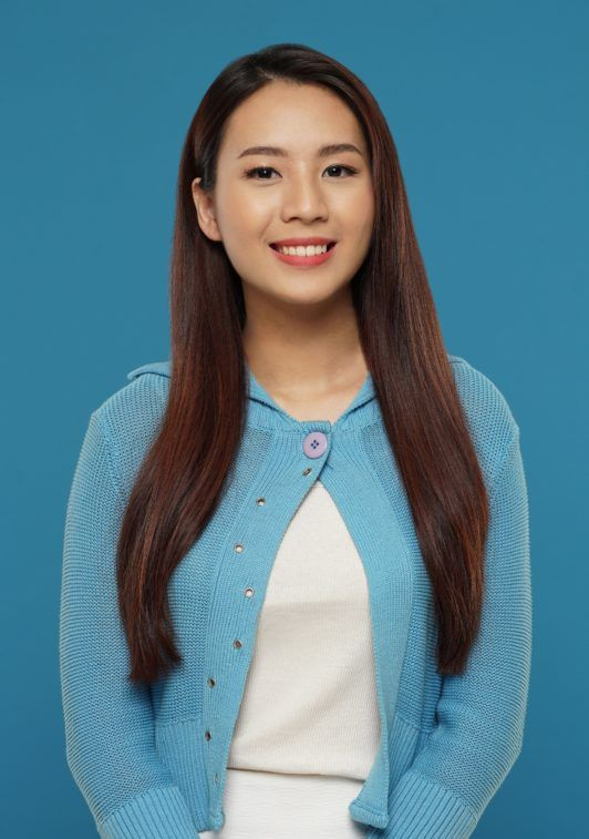 Curly side part hairstyles: Asian woman with long dark brown hair wearing a blue cardigan and white dress against a blue background