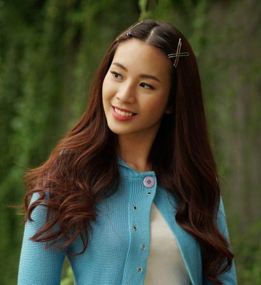 Curly side part hairstyle: Closeup shot of an Asian woman with long dark brown hair with hair clips in outdoor location