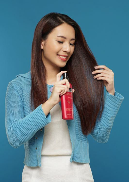 Curly side part hairstyle: Asian woman spraying heat protectant on her long dark brown hair against a blue background