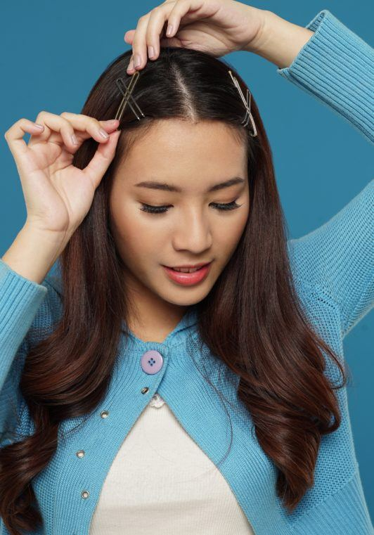 Curly side part hairstyle: Asian woman putting hair clips on her long dark brown hair against a blue background