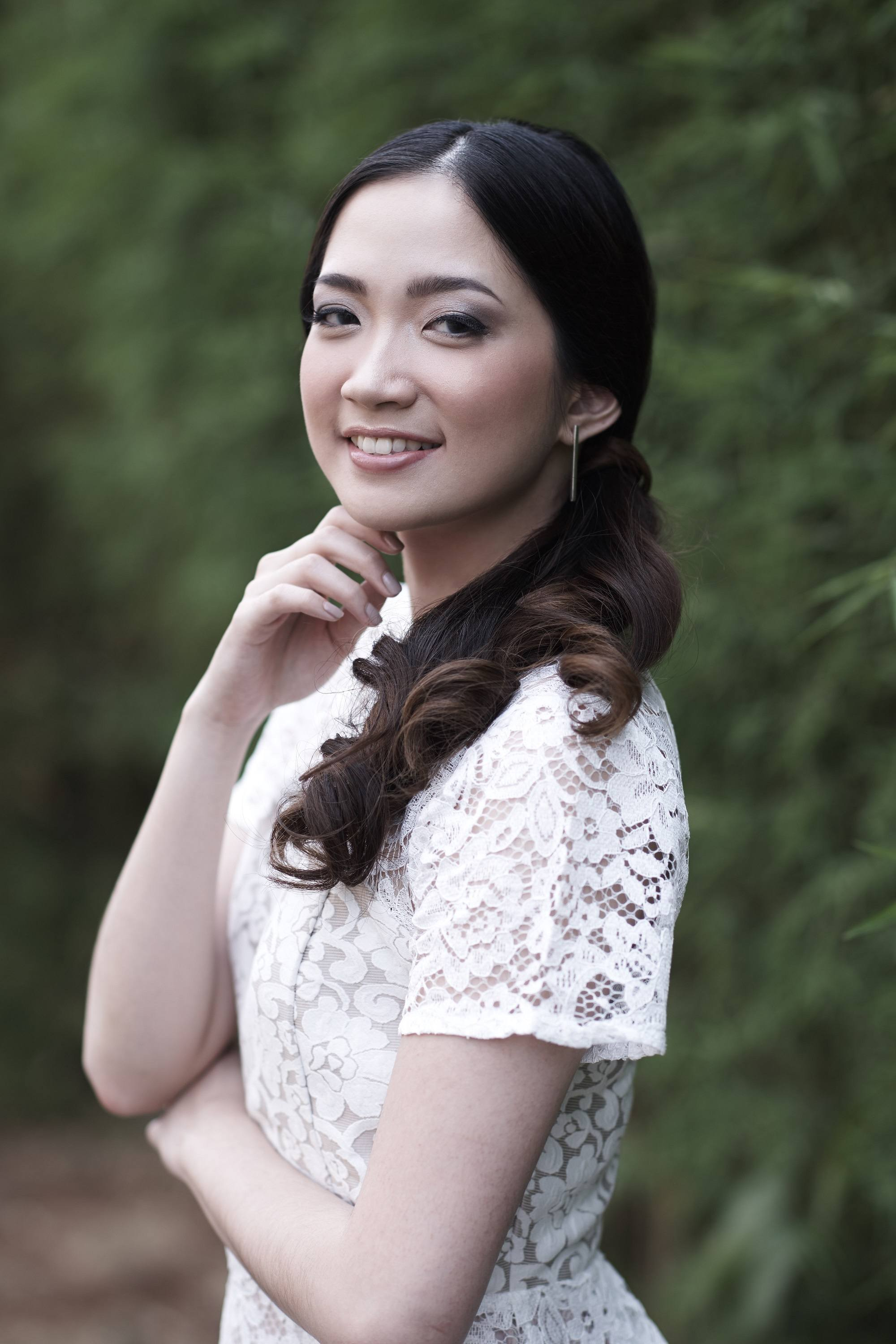 Curly side ponytail: Asian woman wearing a white dress with long black hair in curly side ponytail with leaves in the background
