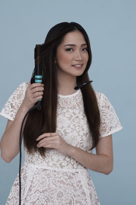 Curly side ponytail: Asian woman wearing a white dress curling her hair against a blue background