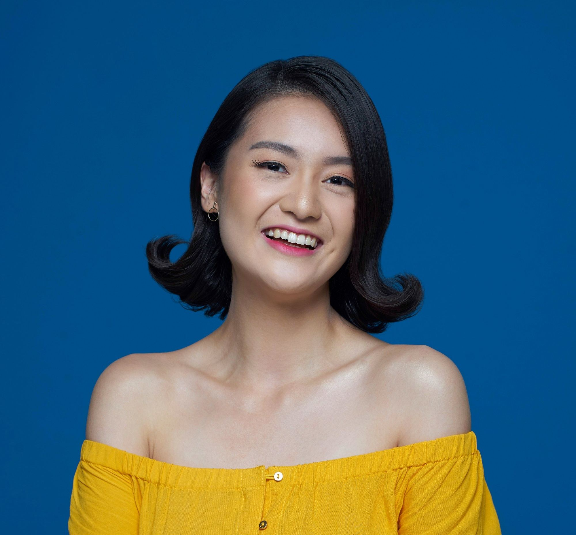 Flipped-out short bob: Closeup shot of an Asian woman with short black hair wearing a yellow dress against a blue background