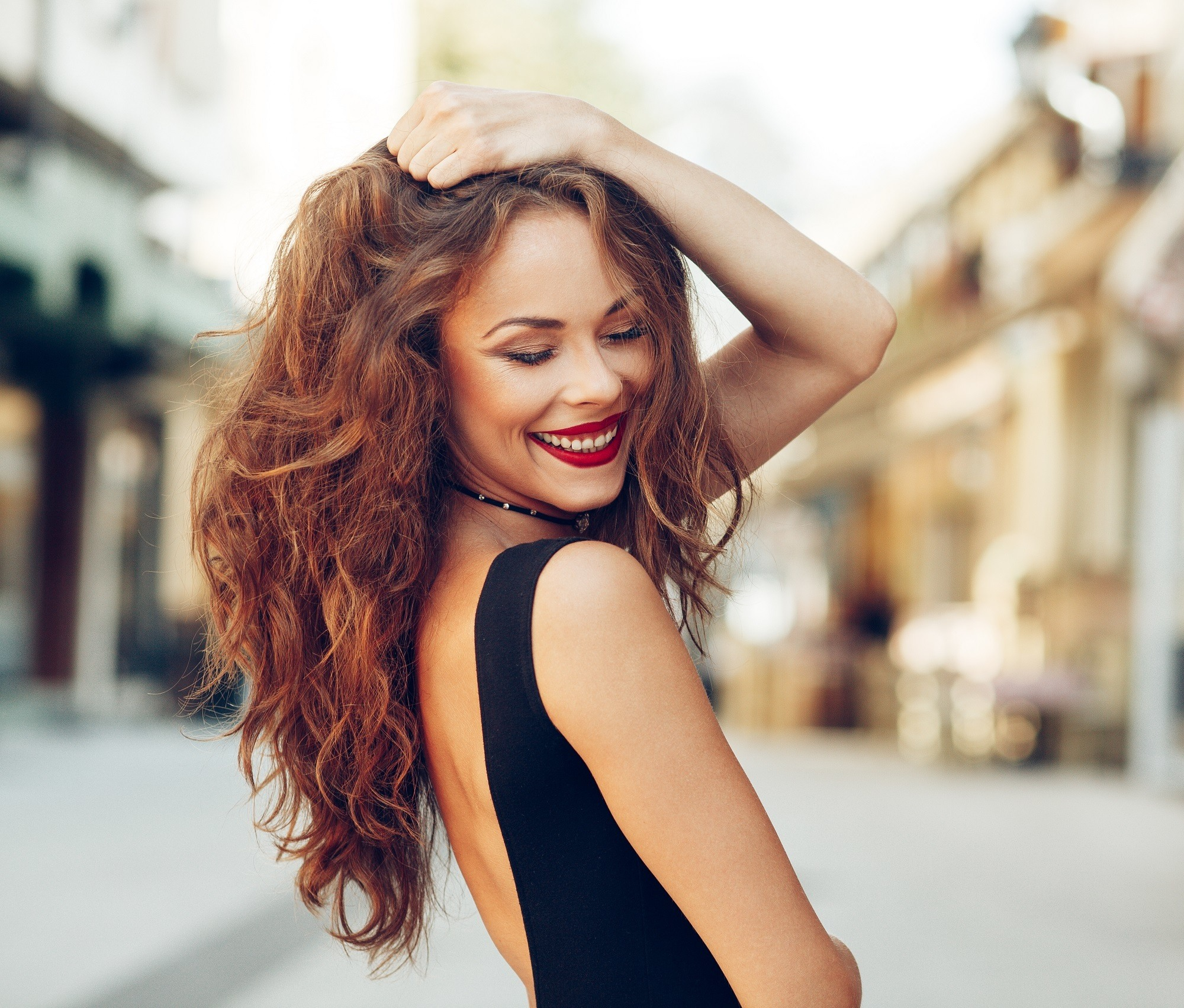 Hair color for curly hair: Woman with long brown curly hair wearing a black sleeveless top outdoors