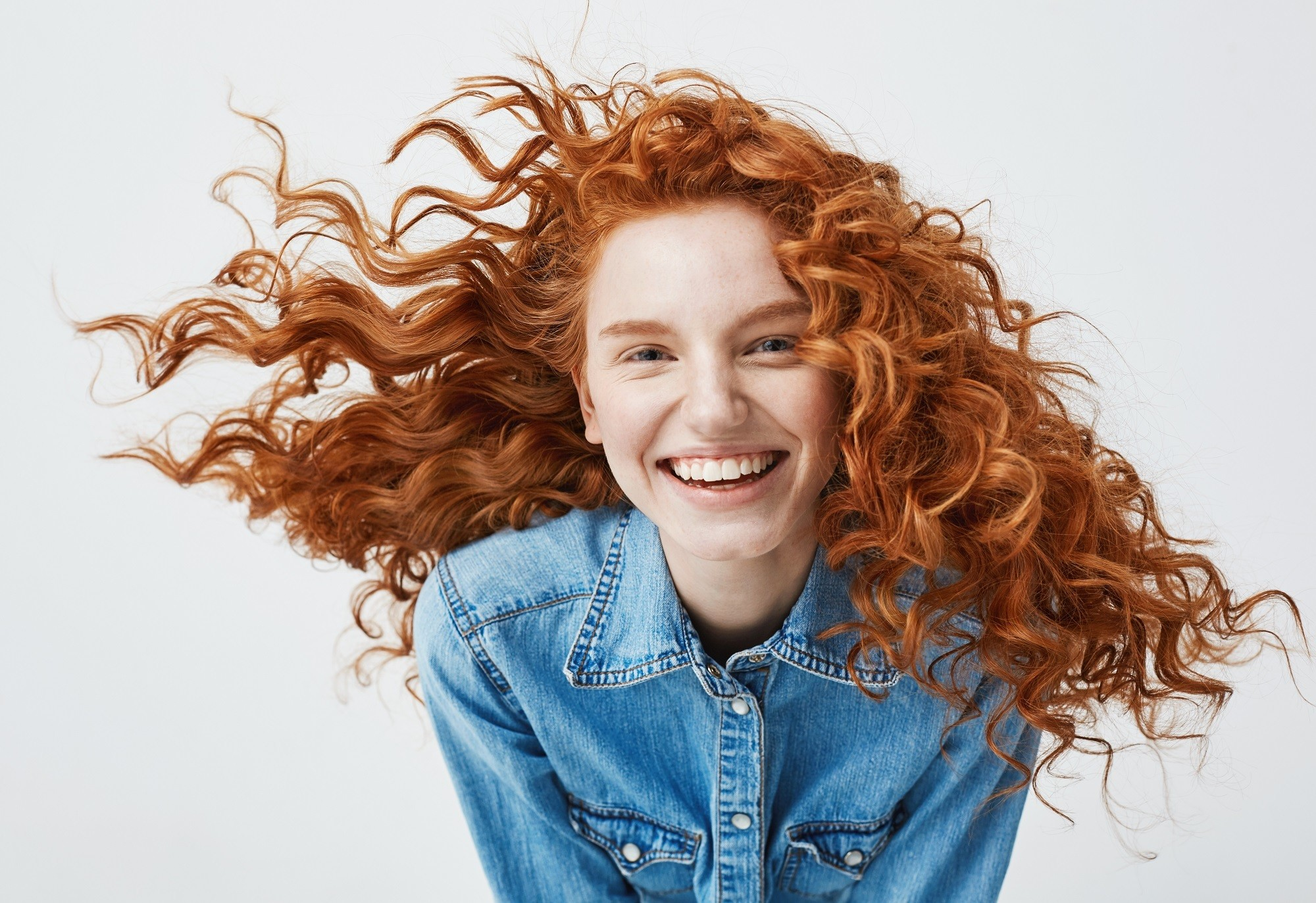 Hair color for curly hair: Closeup shot of a woman with long curly cinnamon hair wearing blue polo against white background