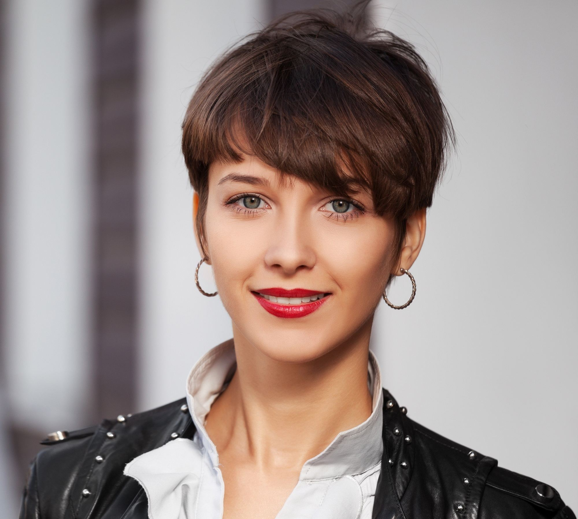 Haircuts for wavy hair: Closeup shot of a woman with brown pixie cut wearing a black jacket outdoors
