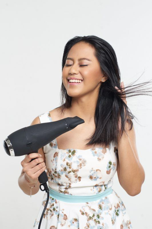 Half ponytail: Asian woman blow drying her black hair against a light gray background