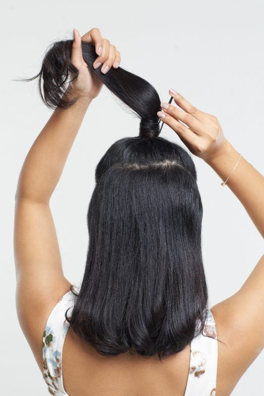 Half ponytail: Back shot of an Asian woman putting a bobby pin on her half ponytail