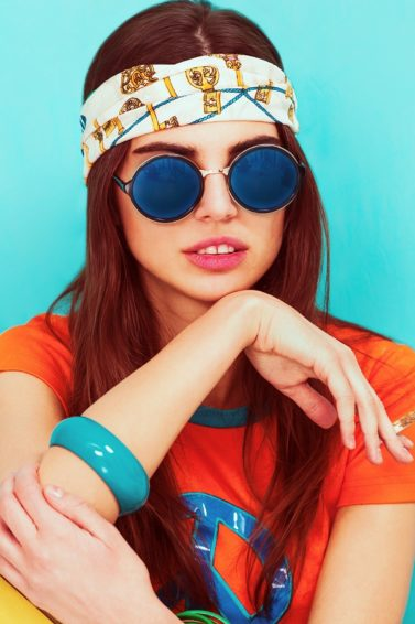 Hippie hairstyles: Closeup shot of woman with long hair and printed headband and wearing an orange shirt against a blue background