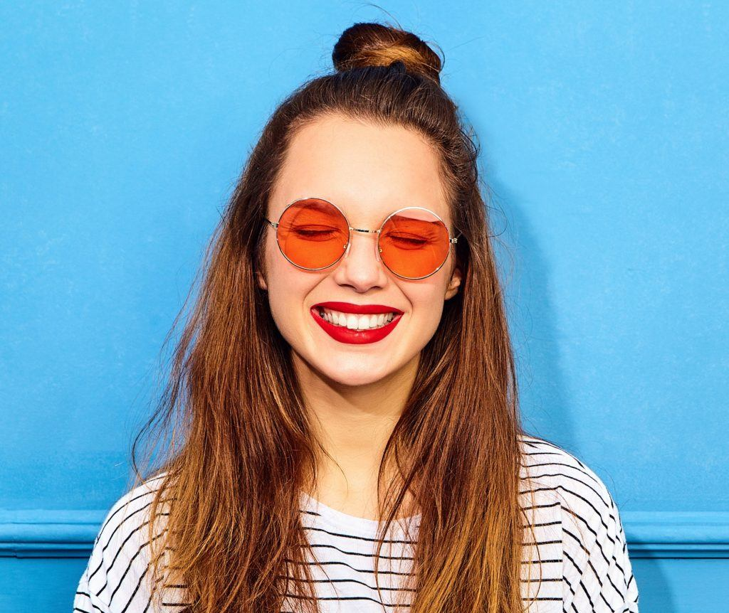 Hippie hairstyles: Closeup shot of a woman with long brown hair in half up top knot wearing shades and standing against a blue background