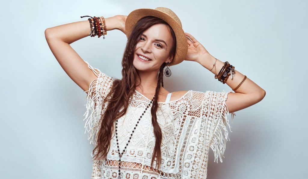 Hippie hairstyles: Woman with long brown hair wearing a white top and hat standing against a white background