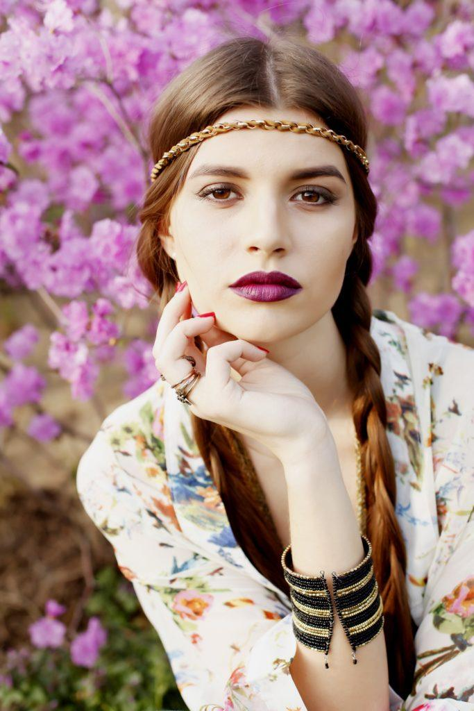 Hippie hairstyles: Closeup shot of a woman with long brown hair in twin braids with headband with purple leaves in the background