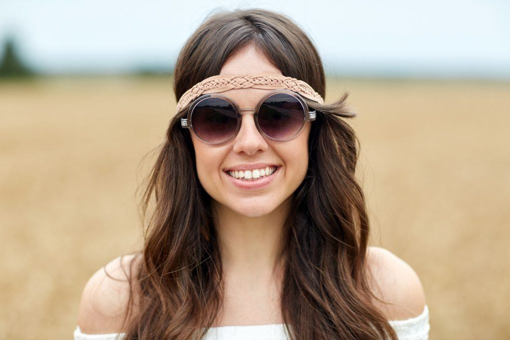 Hippie hairstyles: Closeup shot of woman with long brown wavy hair wearing shades and headband outdoors