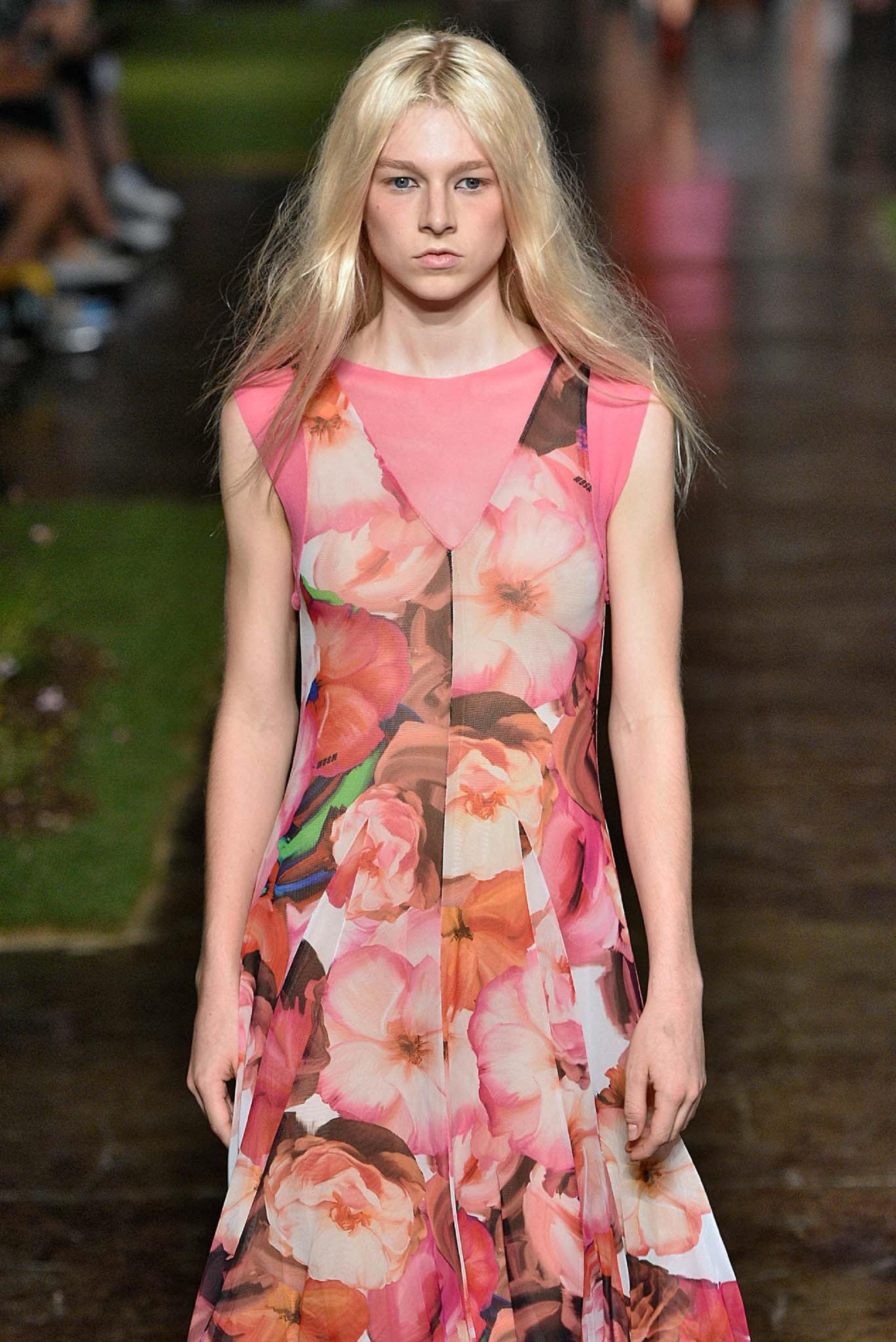 Light blonde hair: White model wearing a printed dress with long blonde hair walking on the runway