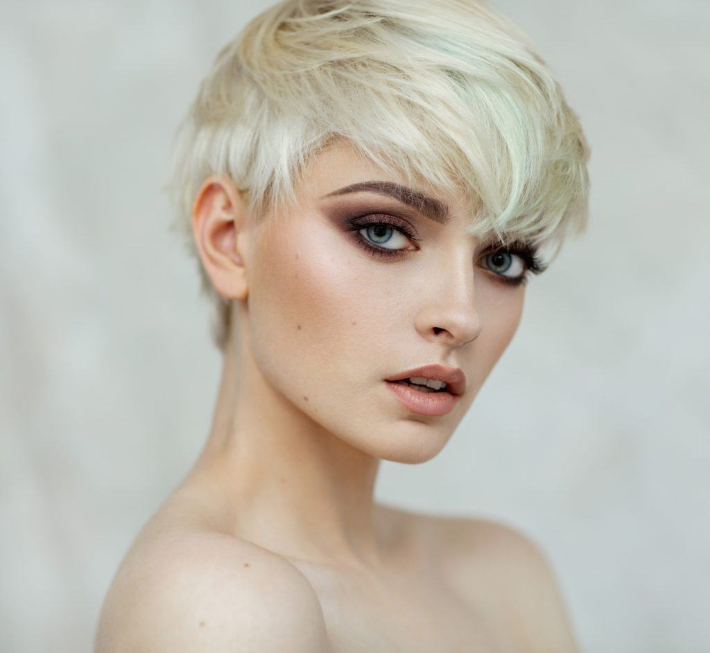 Light blonde hair: Closeup shot of white woman with light blonde pixie cut against white background