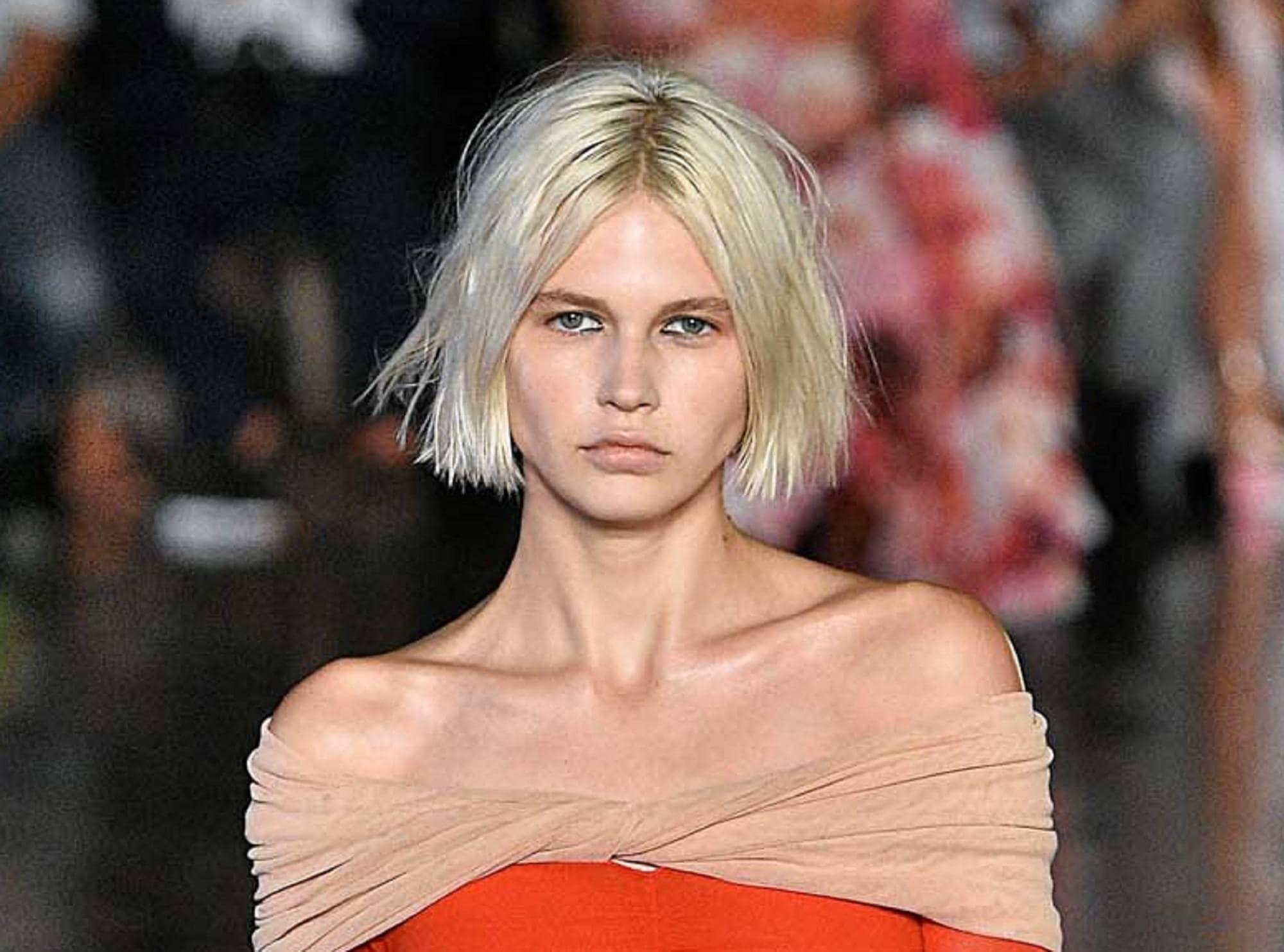 Light blonde hair: Closeup shot of white model with blonde blunt bob walking on the runway